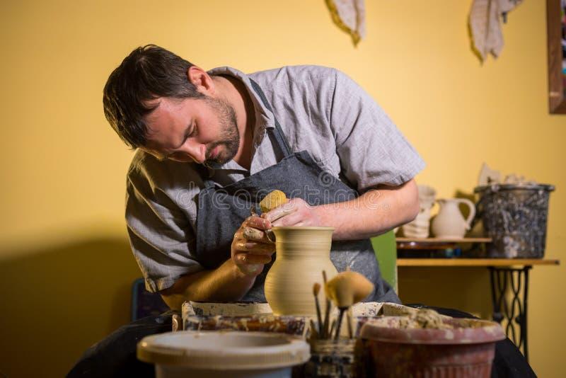 Fachowa męska garncarka pracuje z gliną na garncarki ` s kole zdjęcie stock