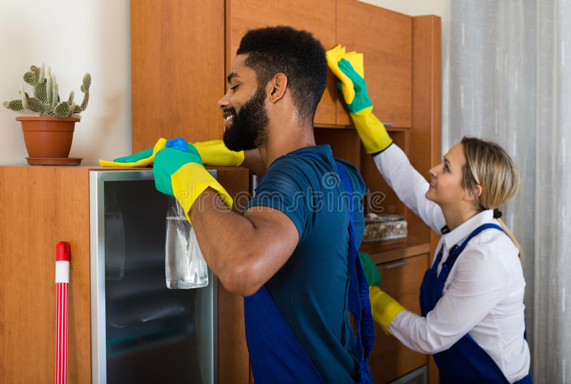 Fachowa para w jednolitym cleaning przy domowym wnętrzem fotografia stock
