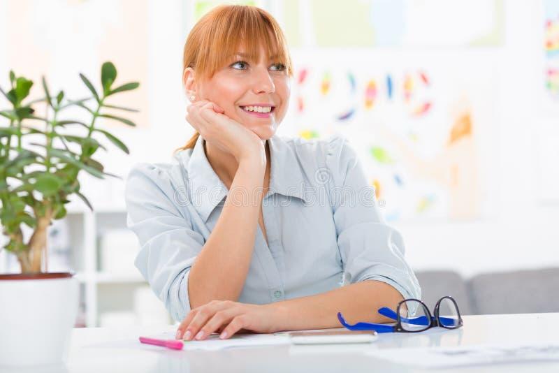 Fachowa piękna młoda kobieta siedzi jej biurko przy ona do domu obrazy stock