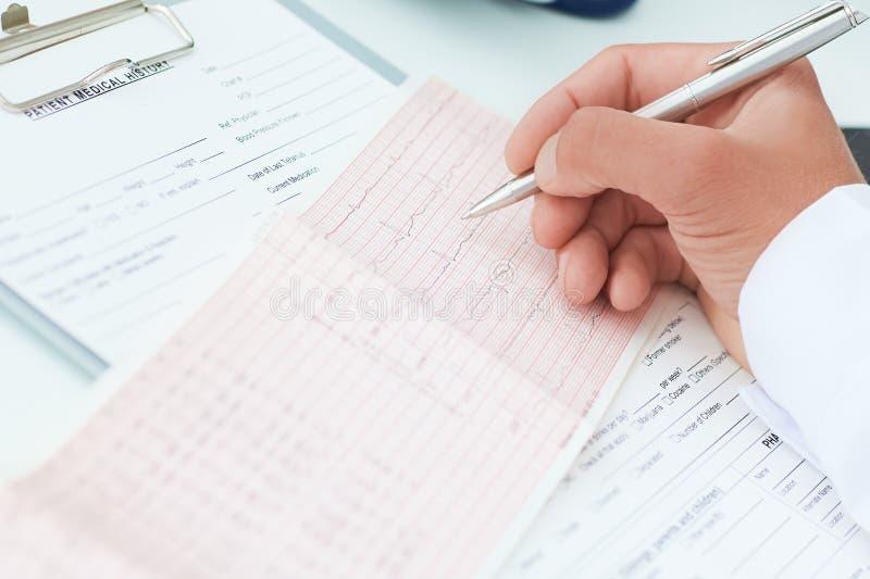Fachowa samiec lekarka wyjaśnia rezultata selectrocardiogram pacjenci Medyczny i healtcare pojęcie zdjęcia stock
