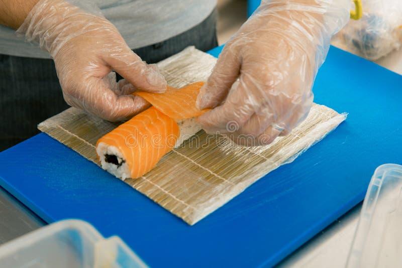 Fachowa suszi szefa kuchni narządzania rolka przy handlową kuchnią Cook stawia łososia na rolce Japońscy kuchnia przepisy zdjęcie stock