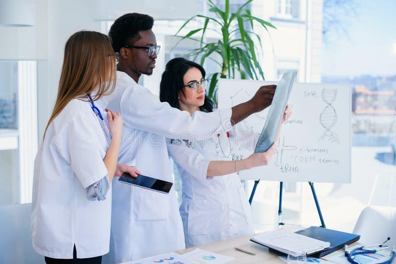 Fachowe lekarki egzamininują pacjenta promieniowanie rentgenowskie Dwa kobiety lekarki wpólnie i jeden samiec doktorskiej praca j obraz stock