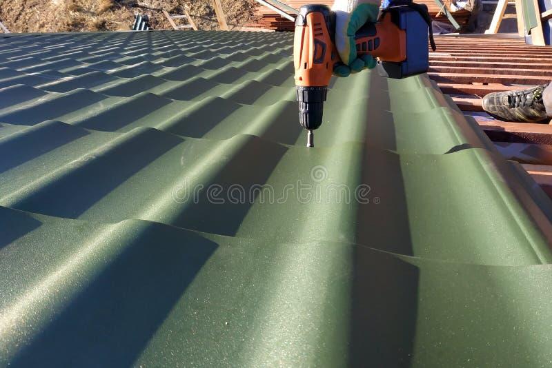 Fachowe pracownik pracy na instalacji dach dach prze?cierad?ami metal tafluj? ?rub? z ?widerem i musztruj? zdjęcia royalty free