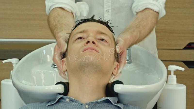 Fachowego fryzjera płuczkowy włosy jej przystojny klient obraz royalty free