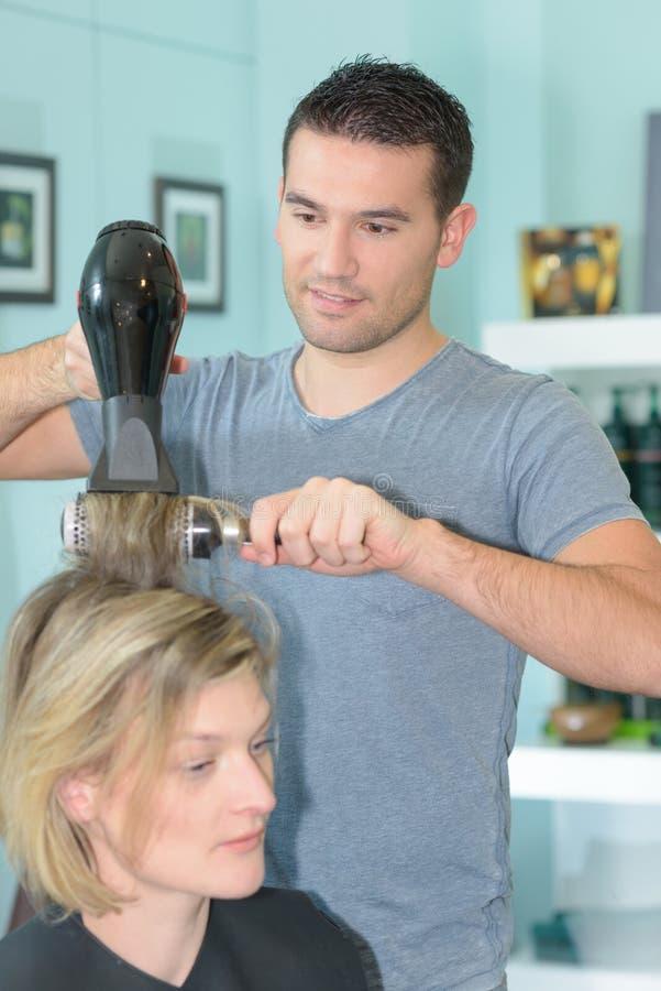 Fachowego fryzjera suszarniczy włosiany klient fotografia stock