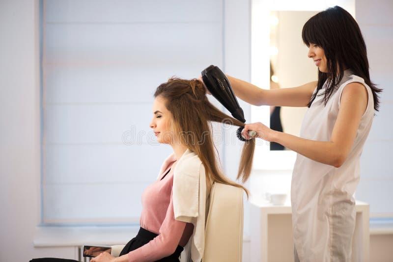 Fachowego fryzjera suszarniczy włosy jej klient fotografia royalty free