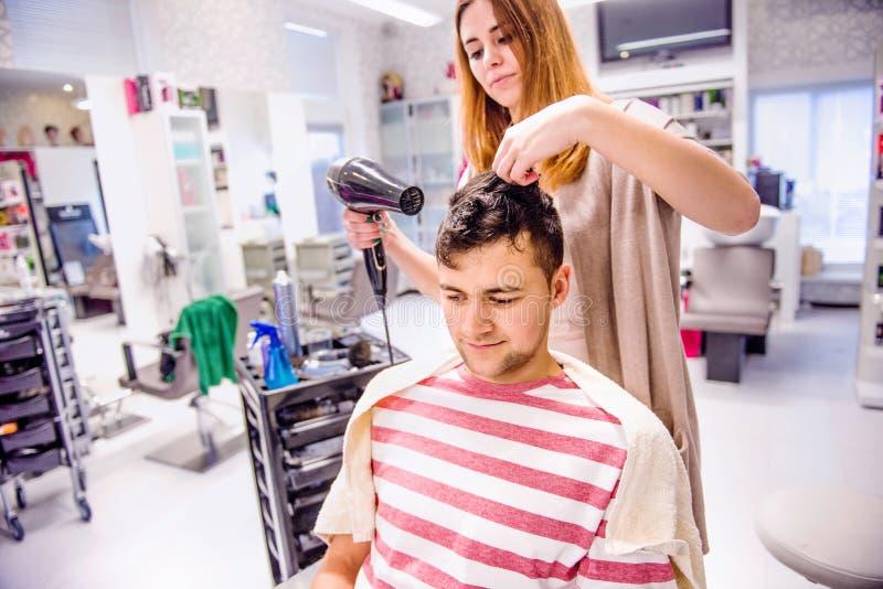 Fachowego fryzjera suszarniczy włosy jej przystojny klient obraz stock