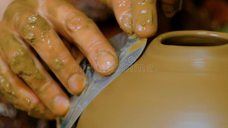 Fachowej garncarki kształtujący puchar z specjalnym narzędziem w ceramicznym warsztacie zdjęcia stock