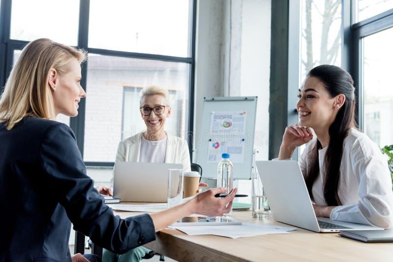 fachowi bizneswomany uśmiecha się each inny podczas gdy pracujący wpólnie obrazy stock