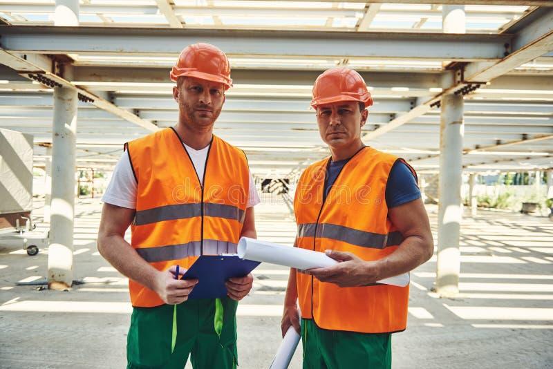 Fachowi budowniczowie w hełmach lokalizują przy pracą fotografia royalty free