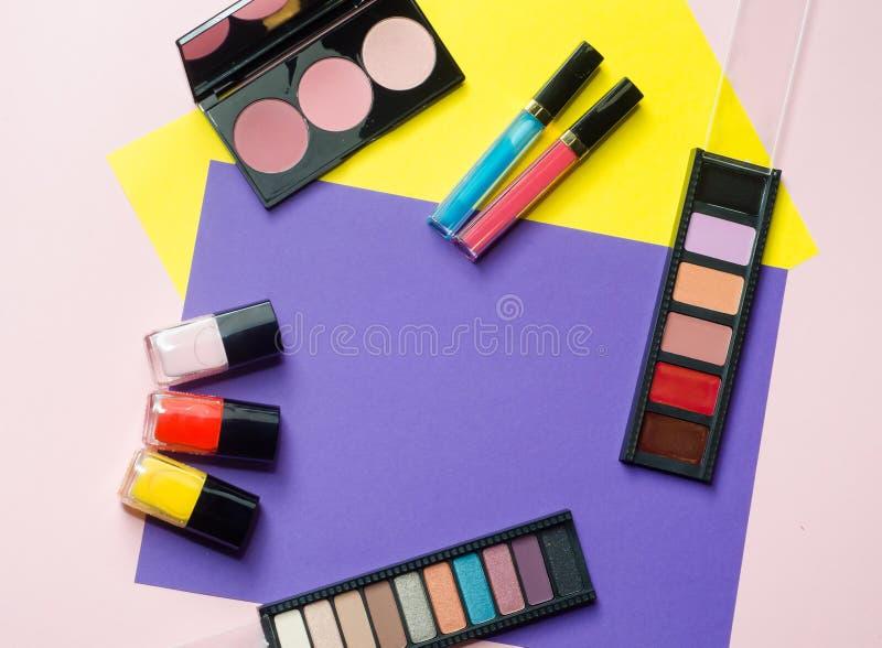 Fachowi kolorowi makeup narzędzia, flatlay na menchii, koloru żółtego i fiołka tle, Palety eyeshadow, rumieniec, pomadka, gwoździ zdjęcie stock