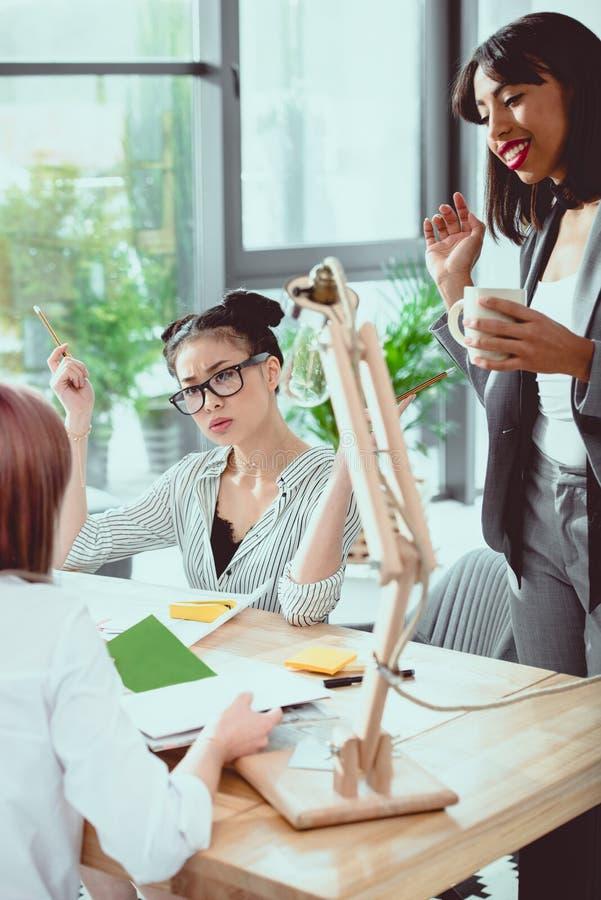 Fachowi młodzi bizneswomany dyskutuje podczas gdy pracujący wpólnie obraz royalty free