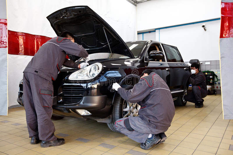 Fachowi samochodowi mechanicy pracuje w auto naprawy stacjach obsługi fotografia royalty free