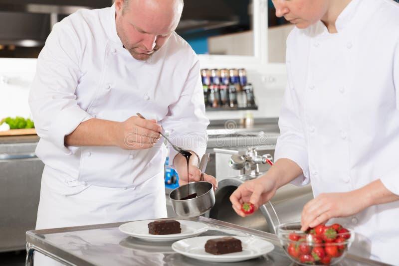 Fachowi szefowie kuchni dekorują deseru tort z cytryna liściem obrazy stock
