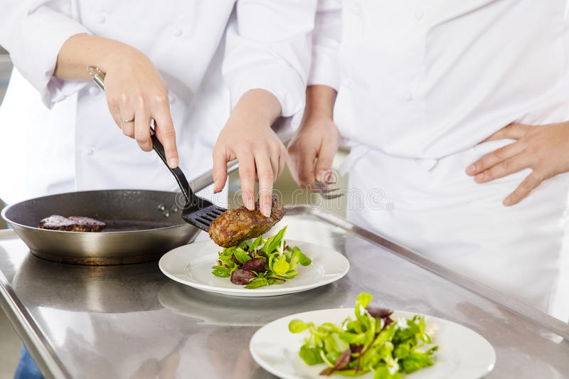 Fachowi szefowie kuchni przygotowywają stków naczynia przy restauracją obrazy royalty free