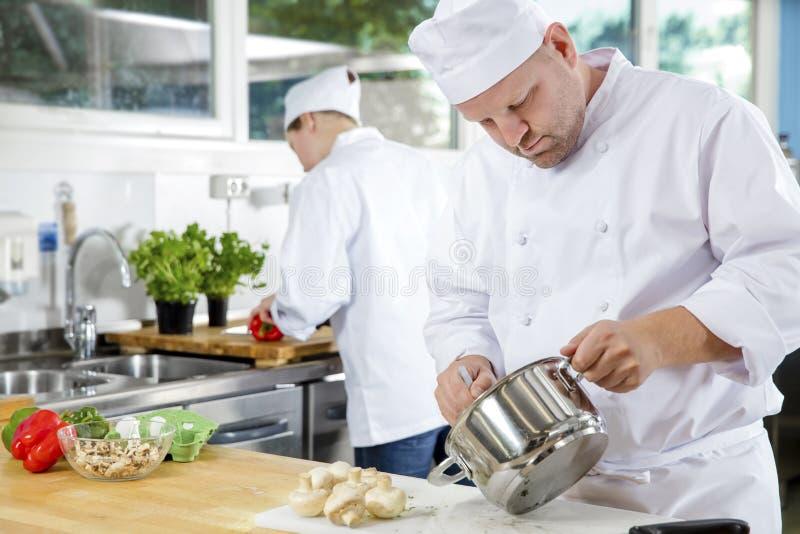 Fachowi szefowie kuchni robią karmowym naczyniom w wielkiej kuchni obraz royalty free