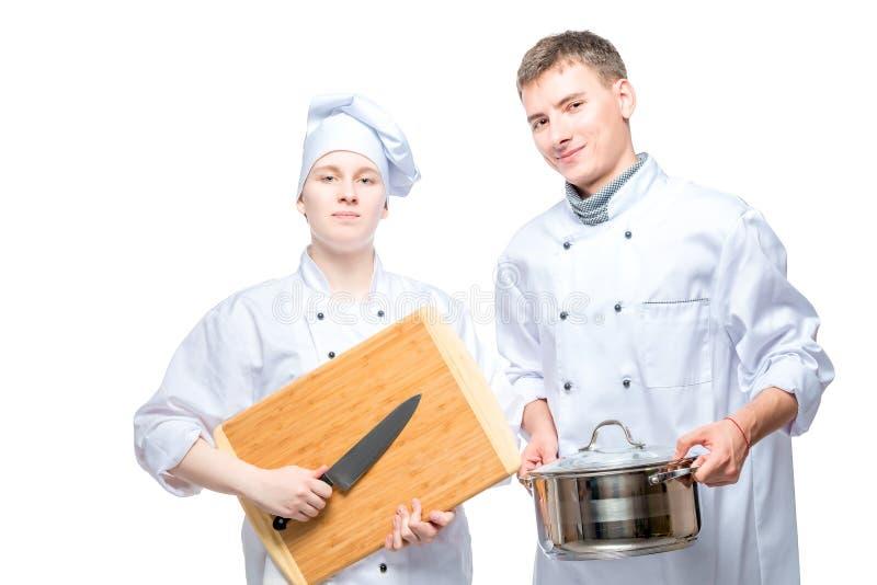 fachowi szefowie kuchni z kuchennymi naczyniami na bielu obrazy stock
