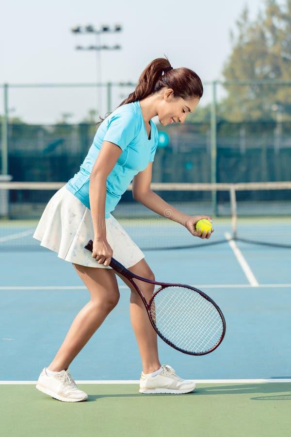 Fachowy żeński gracz ono uśmiecha się podczas gdy słuzyć podczas tenisa dopasowania zdjęcie stock