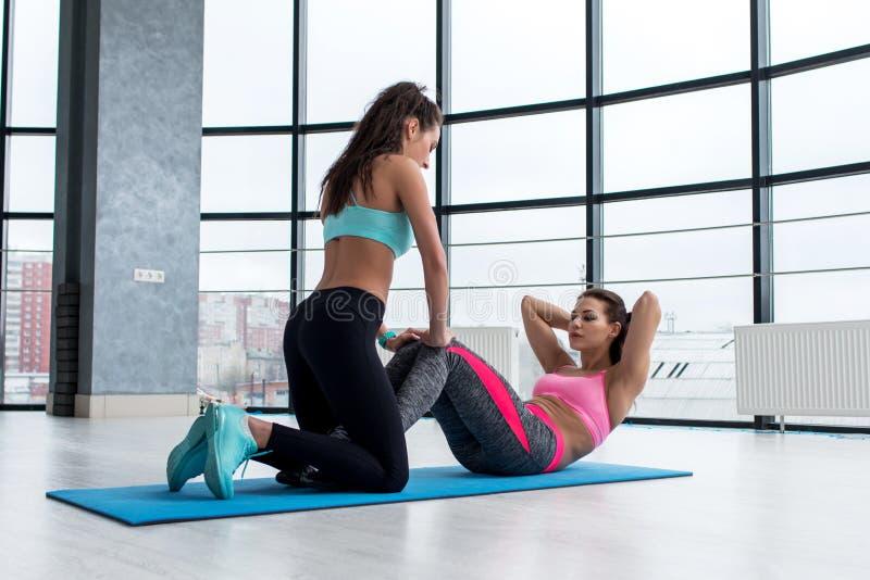 Fachowy żeński osobisty trener pomaga ładnej szczupłej sporty dziewczyny robi brzusznym chrupnięciom kłama na podłoga w gym obrazy stock