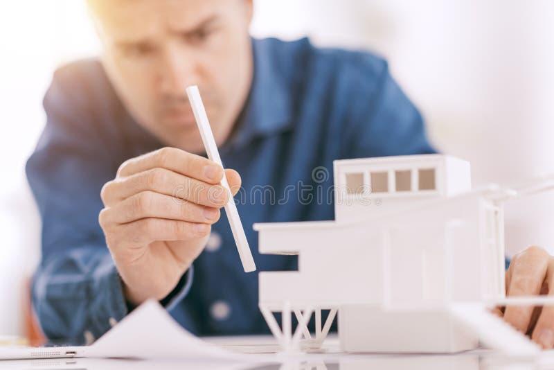 Fachowy architekt pracuje przy biurowym biurkiem, gromadzić architektonicznego modela, projekta i architektury pojęcie, fotografia stock