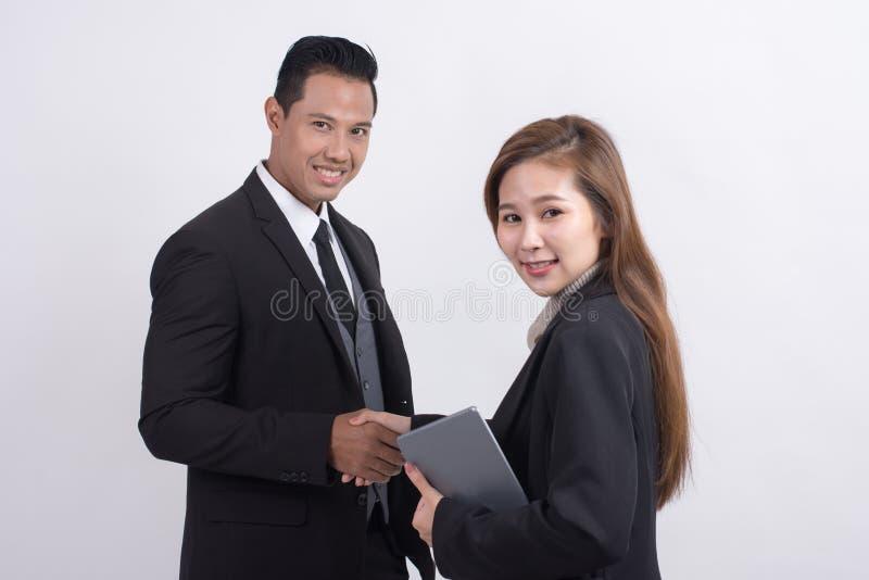Fachowy Azjatycki bizneswoman robi uściskowi dłoni z biznesmenem i patrzeje kamerę obraz royalty free
