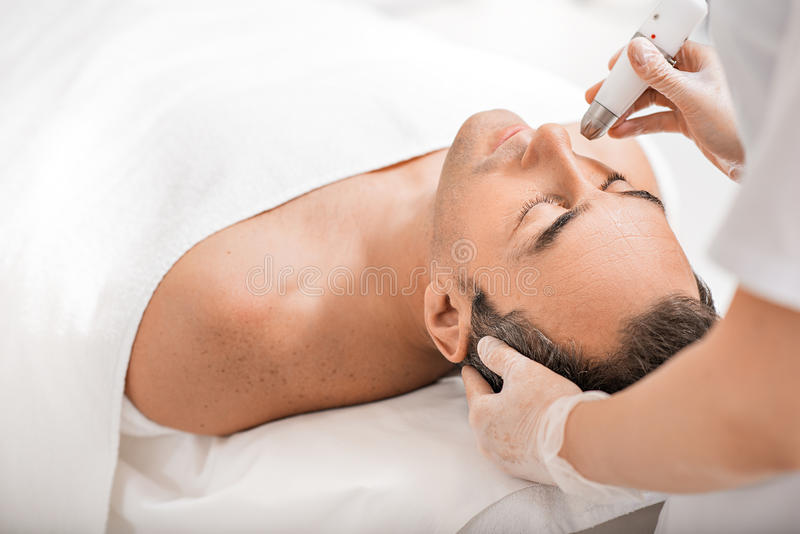 Fachowy beautician odmłodnieje męską twarz fotografia stock