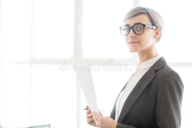 Fachowy bizneswoman trzyma papier w szkłach fotografia royalty free
