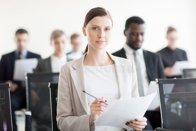 Fachowy bizneswoman z papierem na spotkaniu fotografia royalty free