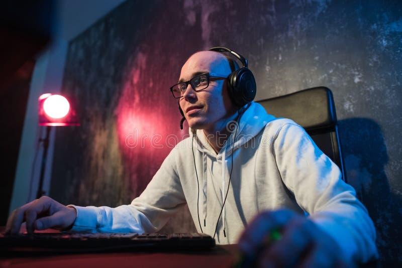 Fachowy chłopiec Gamer Bawić się w Wideo grą na eSports turnieju lub w Internetowej kawiarni Jest ubranym hełmofony i Mówi zdjęcie stock