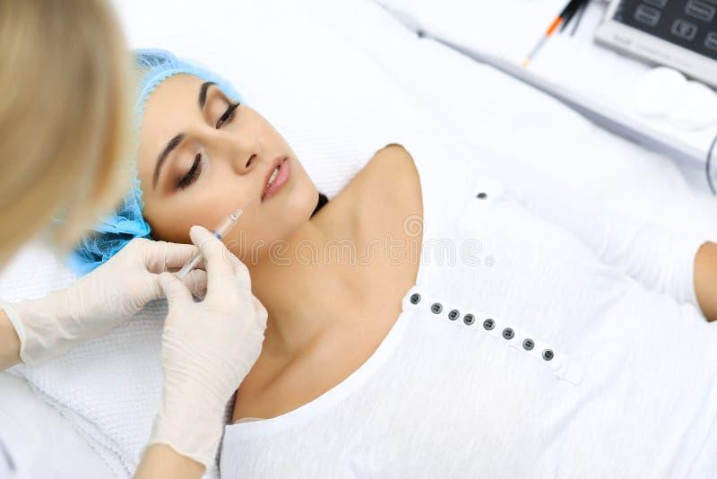 Fachowy cosmetologist robi zastrzykowi w twarzy, wargi Młoda kobieta obrysowywa dostaje strzykawkę z napełniaczem dla twarzy lub fotografia stock