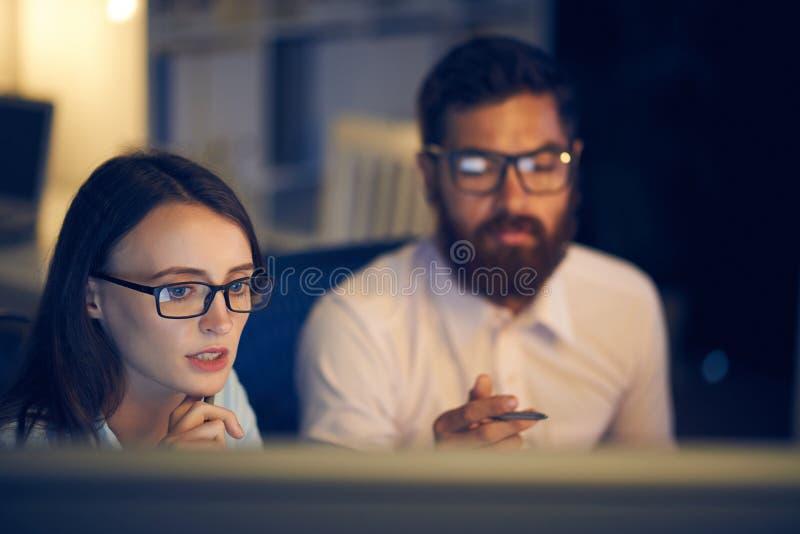 Fachowy coworkers używać komputerowy w biurze póżno obrazy royalty free