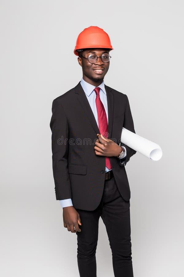 Fachowy czarny architekt odwiedza budowę z projektów planami i ochronnym zbawczym ciężkim kapeluszem odizolowywającymi na bielu obraz royalty free