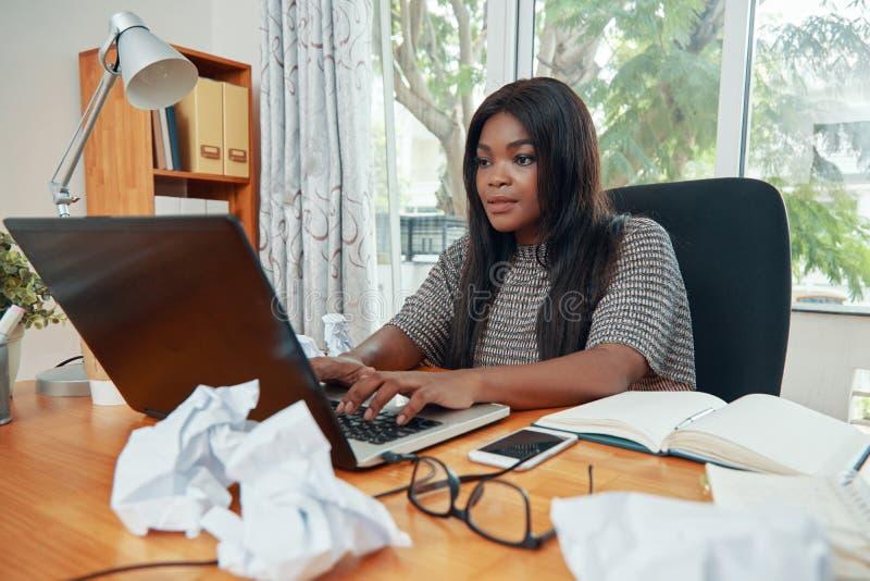 Fachowy czarny bizneswoman pracuje przy biurkiem zdjęcia stock