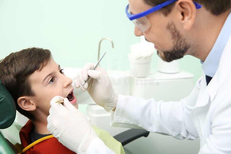 Fachowy dentysta pracuje z małym pacjentem w klinice obraz royalty free