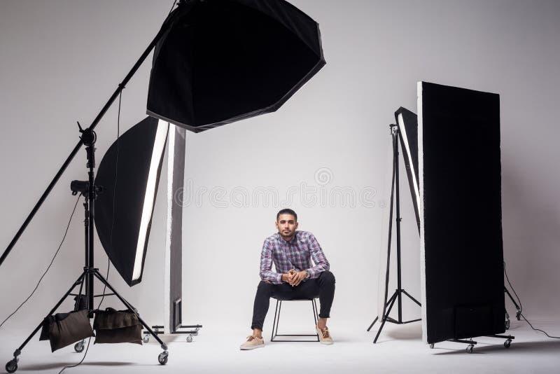 Fachowy fotografii studio pokazuje za scenami za?wieca fasonuje przystojnego młodego człowieka modela przy studiiem w lekkich bły obrazy stock