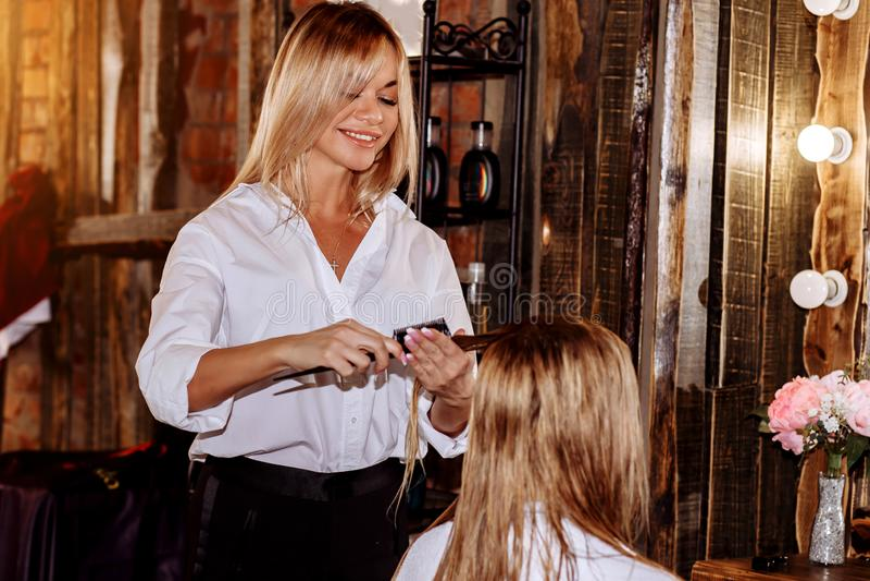 Fachowy fryzjer pracuje z klientem w pi?kno salonie Pi?kna kobieta ono u?miecha si? patrzej?cy jej odbicie w lustrze przy w?osy zdjęcia royalty free