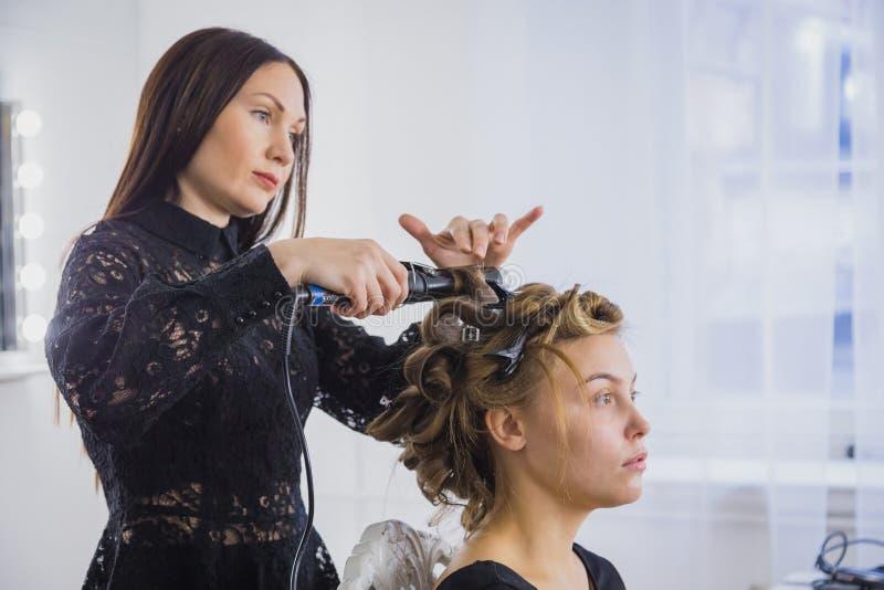 Fachowy fryzjer robi fryzurze dla młodej ładnej kobiety - robić fryzuje obrazy stock
