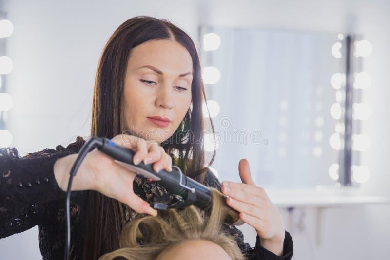 Fachowy fryzjer robi fryzurze dla młodej ładnej kobiety - robić fryzuje zdjęcia stock