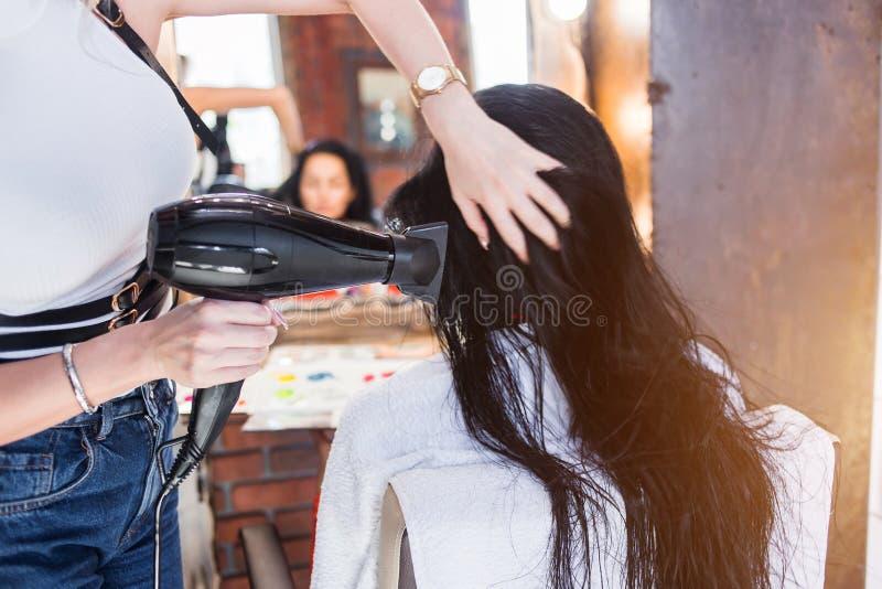 Fachowy fryzjer z hairdryer suszy włosy w salonie zdjęcia stock