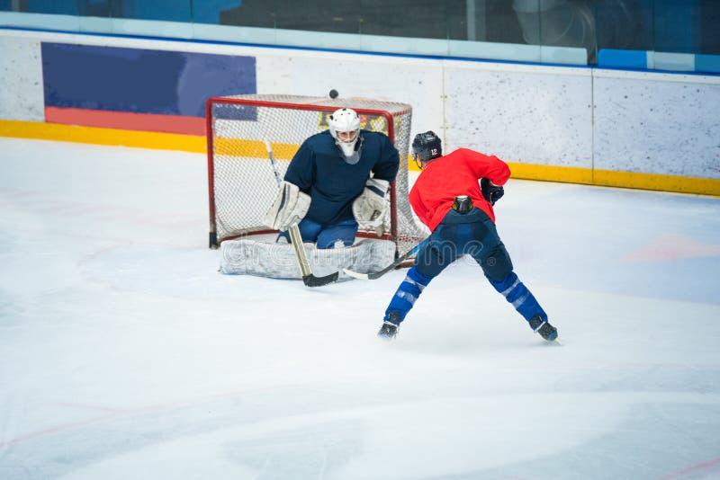Fachowy hokeja na lodzie gracz na hokeja na lodzie stadium pociągu wraz z bramkarzem Bawi się fotografię, redaguje przestrzeń, zi zdjęcie royalty free
