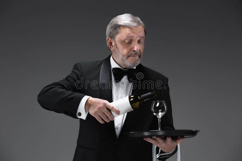 Fachowy kelner w mundurze słuzyć wino fotografia stock