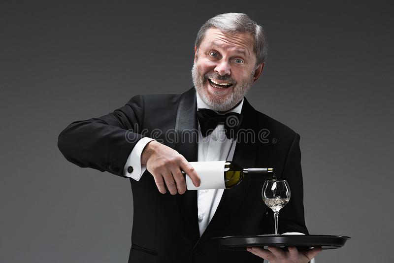 Fachowy kelner w mundurze słuzyć wino obrazy stock