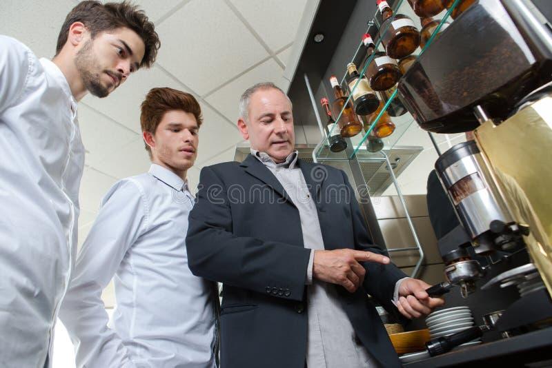 Fachowy kelner wyjaśnia ucznia dobrego sposób przygotowywać kawę fotografia royalty free