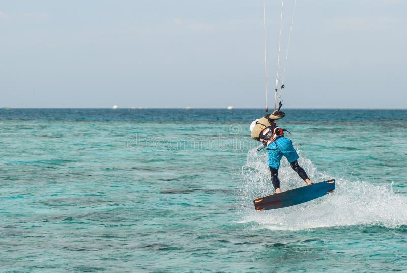 Fachowy kiter robi trudnej sztuczce na pięknym tle kiść i ocean powierzchnia obrazy royalty free