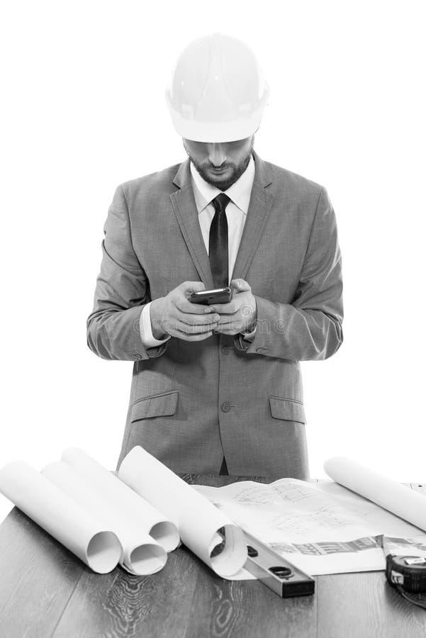 Fachowy męski architekt używa jego mądrze telefon obrazy stock