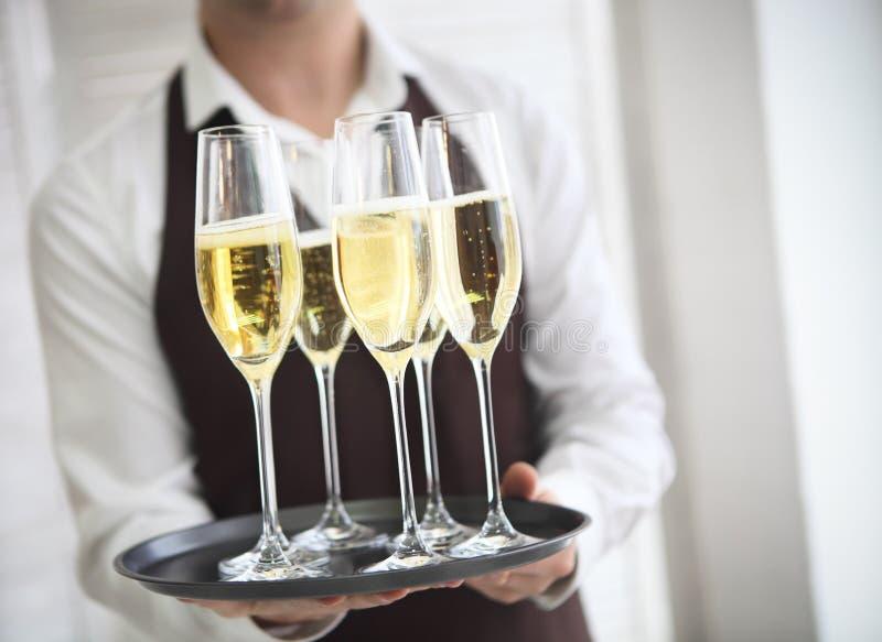 Fachowy męski kelner w jednolitym porcja szampanie zdjęcie stock