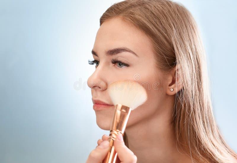 Fachowy makeup artysta stosuje makeup na twarzy młoda kobieta w piękno salonie zdjęcia stock