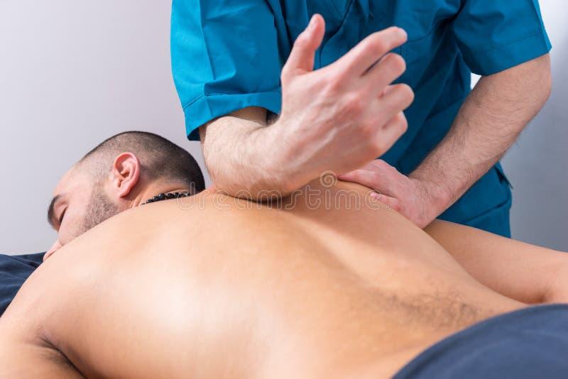 Fachowy masażysta robi kręgosłupa masażowi zdjęcia royalty free