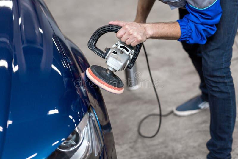 Fachowy mechanik używa władzy odbojnicy maszynę dla czyścić ciało samochód od narysów zdjęcia royalty free