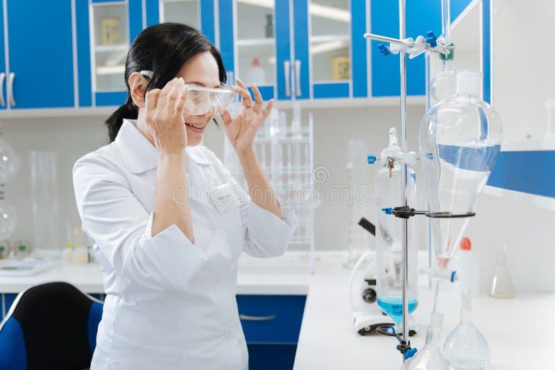 Fachowy medyczny badacza kładzenie na ochronnych szkłach fotografia stock